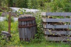 Gammal trätrummastandig bredvid en trädgårds- kompost Arkivbild