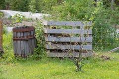 Gammal trätrummastandig bredvid en trädgårds- kompost Arkivfoton