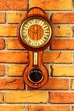 Gammal träväggklocka med barometern och termometern på det bric royaltyfri fotografi