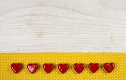 Gammal trävit bakgrund med sju röda hjärtor på gulingen Arkivbilder