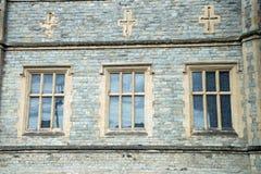 Gammal traditionell engelsk arkitektur, tre fönster och kors över royaltyfria bilder