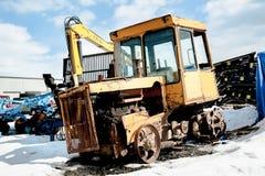 Gammal traktor bland ny utrustning Tyumen Ryssland Arkivbild