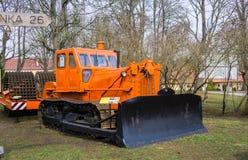 Gammal traktor för att bära ut jordbruks- arbete i ett fält på en lantgård 7 April 2019 latvia royaltyfri fotografi