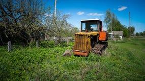 Gammal traktor i byn Arkivbild