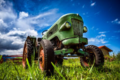 Gammal traktor i de alpina ängarna Arkivbild
