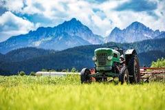 Gammal traktor i de alpina ängarna Fotografering för Bildbyråer