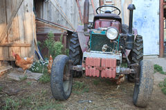 Gammal traktor i en by Arkivfoton