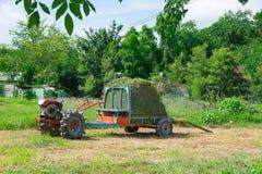 Gammal traktor med gräs eller hö på släpet åkerbrukt medel Royaltyfri Fotografi