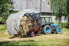 Gammal traktor med hö, jordbruks- plats Arkivbild