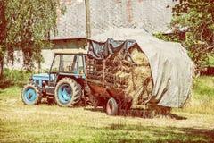 Gammal traktor med hö, jordbruks- plats, gult filter Arkivbilder