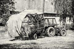 Gammal traktor med hö, jordbruks- plats som är akromatisk Royaltyfria Bilder