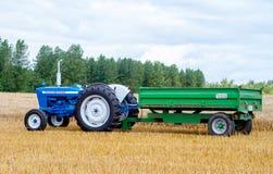 Gammal traktor och släp för tappningvadställe 4000 i skördfält Royaltyfria Bilder