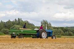 Gammal traktor och släp för tappningvadställe 4000 i skördfält Arkivfoto
