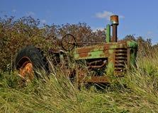 Gammal traktor som döljas av långt gräs, Arkivbild