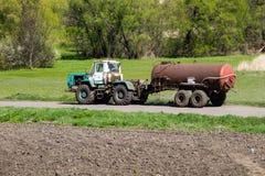 Gammal traktor som kör på den lantliga vägen Royaltyfria Bilder