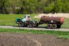 Gammal traktor som kör på den lantliga vägen Royaltyfri Foto