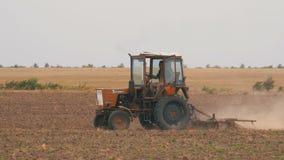 Gammal traktor som plogar fältet stock video