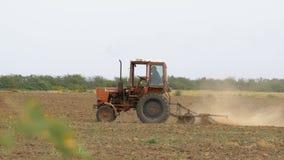 Gammal traktor som plogar fältet lager videofilmer