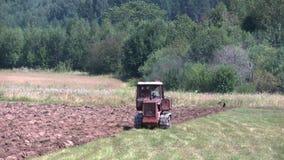 Gammal traktor som plogar jorden bonde arkivfilmer
