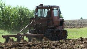 Gammal traktor som plogar jorden Farmer9 arkivfilmer
