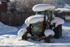 Gammal traktor under snön Arkivfoton