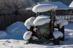 Gammal traktor under snön Royaltyfria Bilder