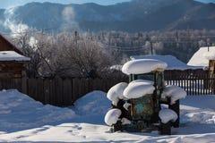 Gammal traktor under snön Arkivfoto