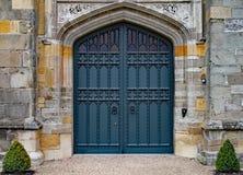 Gammal tung utsmyckad dörr i en gammal engelsk mangårdsbyggnad arkivfoto