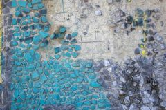 Gammal tungt skadad grå betongvägg med målade gröna, svarta och gula stenar av olika former och format ungefärlig yttersida arkivfoto