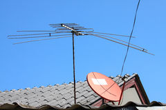 Gammal TVantenn på hustaket med blå himmel Royaltyfri Bild