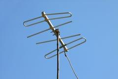 Gammal TVantenn på hustaket med blå himmel Royaltyfri Fotografi