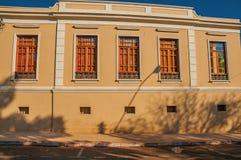Gammal utsmyckad radhusfasad mycket av fönster i en tom gata på en solig dag på San Manuel royaltyfria foton