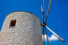 Gammal väderkvarn med blå himmel och vita moln Gamla ställen för livsmedelsproduktion Stenbyggnad med lång historia royaltyfri foto