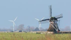 Gammal väderkvarn med moderna väderkvarnar i bakgrunden Arkivfoton