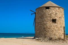 Gammal väderkvarn på stranden fotografering för bildbyråer
