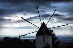 Gammal väderkvarn som ser till den molniga solnedgånghorisonten Arkivbilder
