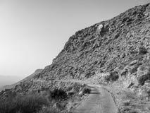 Gammal väg på den torra steniga backen i öknen i svartvitt royaltyfri fotografi