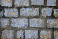 Gammal vägg av beigea kvarter av den Jerusalem stenen med exfoliating målarfärglagertextur Royaltyfria Bilder