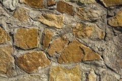 Gammal vägg av gula stenar av olika format och former i grått cement Textur för grov yttersida royaltyfria foton