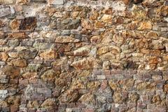 Gammal vägg av tegelstenar och stenar Arkivbild