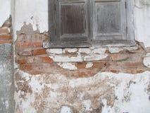Gammal vägg för röd tegelsten, med det gamla fönstret, med sprucken konkret bakgrundstextur Royaltyfri Fotografi