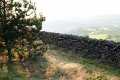 Gammal vägg för torr sten i welsh bygd, berg i bakgrund Arkivbilder