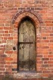 Gammal vägg med en liten dörr Royaltyfria Foton