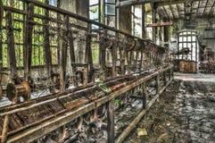 Gammal väva vävstol och roterande maskineri på en övergiven fabrik Arkivfoto