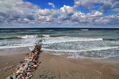 Gammal vågbrytare på den sandiga stranden av det baltiska havet Royaltyfri Bild