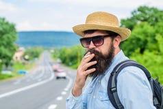 Gammal vana Man med skägget och mustasch i sugrörhatt som röker cigaretten, defocused vägbakgrund Stilfull handelsresande arkivfoton