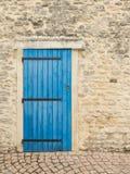 Gammal vägg med den blåa antika dörren Royaltyfria Bilder