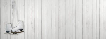 Gammal vit åker skridskor för konståkning på en vit wood tappning eller en grungy bakgrund arkivbild