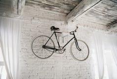 Gammal vit cykelwhist på en vit stenvägg arkivfoton