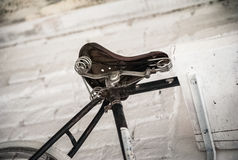 Gammal vit cykelwhist på en vit stenvägg arkivbilder